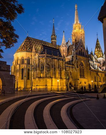 The outside of Matthias Church in Budapest Hungary at night shownig the gothic architecture. poster