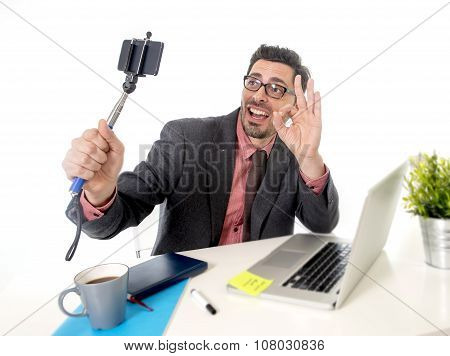 Funny Nerd Businessman At Office Desk Taking Selfie Photo With Mobile Phone Camera And Stick