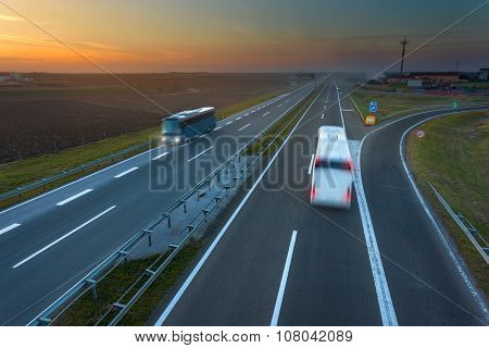 Two Buses In Motion Blur On The Highway At Sunset