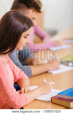 Young girl is busy making notes.