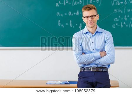 Young male professor is posing at the desk.