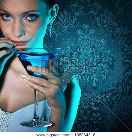 Beautiful woman with martini glass on damask wallpaper background