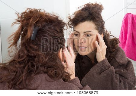 Middle-aged woman looking at her wrinkles