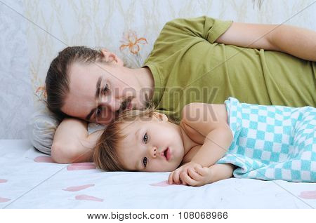 Cute baby ailing and lying with daddy sad poster