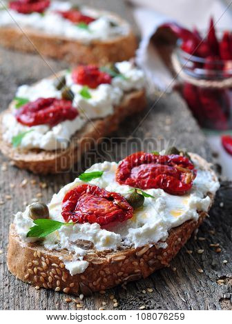 toast of rye bread with different seeds with ricotta cheese, sun-dried tomatoes, capers, parsley and