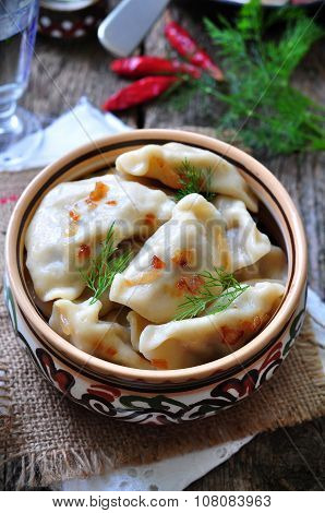 Dumplings with potatoes and mushrooms with fried onions in a traditional ceramic plate on a wooden table. Ukrainian traditional cuisine. rustic style. selective focus poster