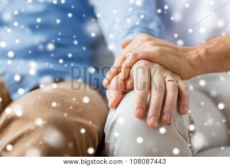 people, homosexuality, same-sex marriage, gay and love concept - close up of happy male gay couple holding hands with wedding rings on over snow effect poster