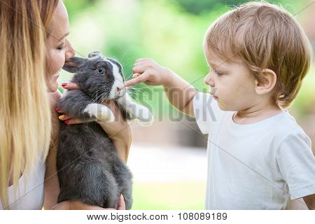 Little boy touching pet rabbit's nose while young woman is holding pet