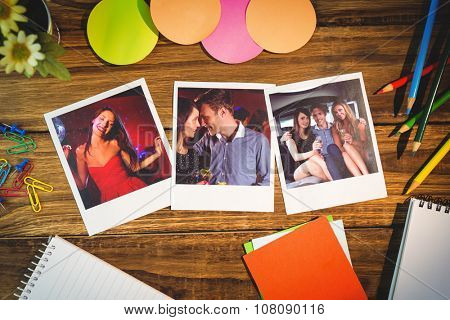 Overhead view of office supplies with blank instant photos against pretty brunette dancing and smiling
