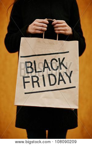 Girl showing paperbag inviting to Black Friday