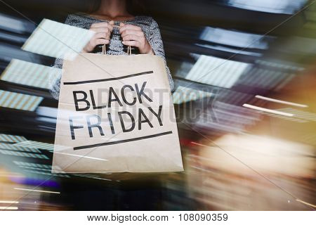 Shopper holding Black Friday paperbag during sale in the mall
