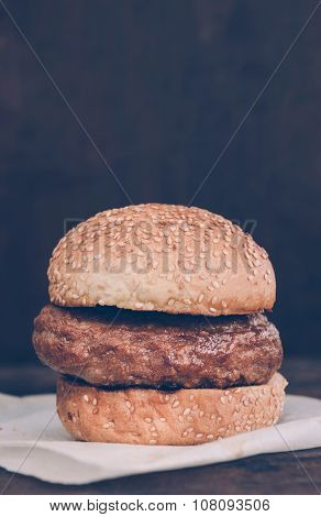 Beef burger in the bun on wooden background with blank space poster