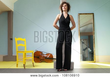 Portrait of young cellist, inside room