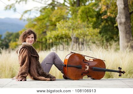 Portrait of young cellist, outdoors