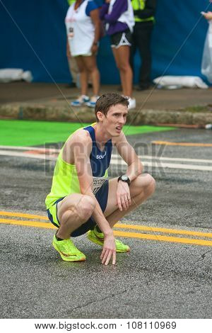 Exhausted Runner Kneels To Catch Breath At Peachtree Road Race