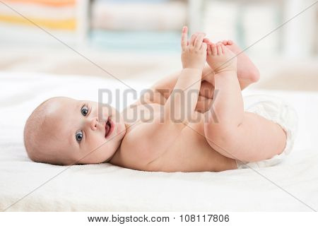 baby girl lying on white bed and holding her legs