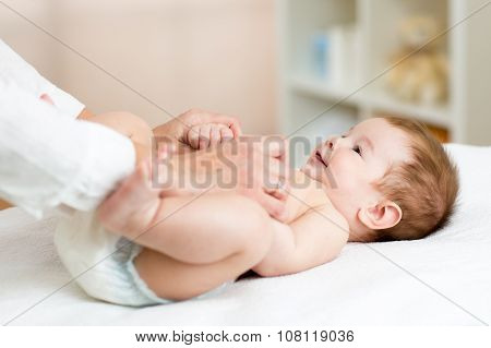 Masseuse or doctor massaging baby boy