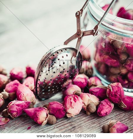 Rose Buds Tea, Tea Strainer And Glass Jar On Rustic Wooden Table. Retro Stylized.