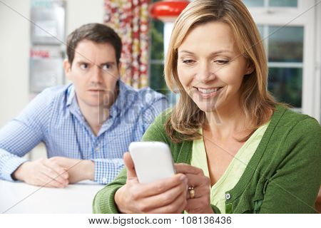 Unhappy Man Sitting At Table As Partner Texts On Mobile Phone