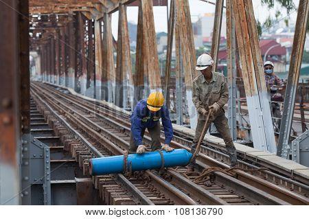 Asian bridge builders working on old vintage Long Bien bridge