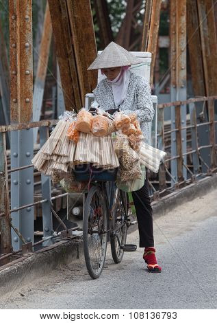 Asian vendor wearing conical hat carrying street food on a bicycle