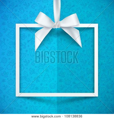 White paper gift box frame with silky bow and ribbon on blue Christmas pattern background