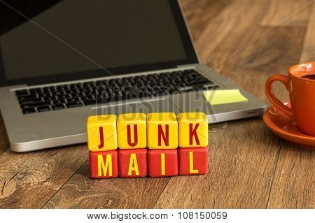 Junk Mail written on a wooden cube in front of a laptop