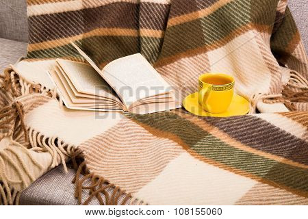 Cup With Tea And The Open Book On A Checkered Woolen Plaid