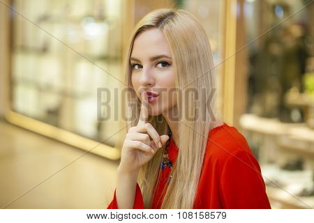 Portrait of attractive girl with finger on lips, concept of student show quiet, silence, secret gesture, young pretty blonde woman in red dress
