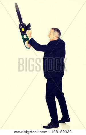 Furious mature businessman with chainsaw.  poster