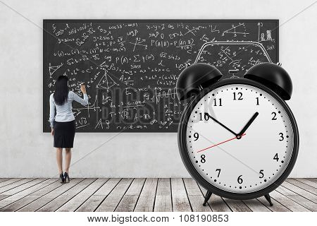 Rear View Of Business Lady Who Is Writing Math Formulas On The Black Chalkboard. The Huge Alarm Cloc