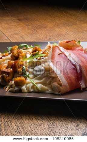 Decorated tagliatelle with cheese sauce, mushrooms and chicken