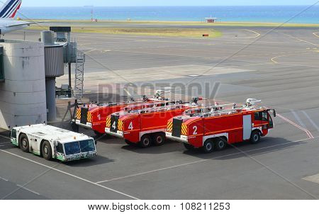 SAINT DENIS, REUNION ISLAND, FRANCE - NOVEMBER 9, 2015: The Fire Fighting Trucks ready for action on Roland Garros Airport near Indian Ocean coast. Accident prevention.
