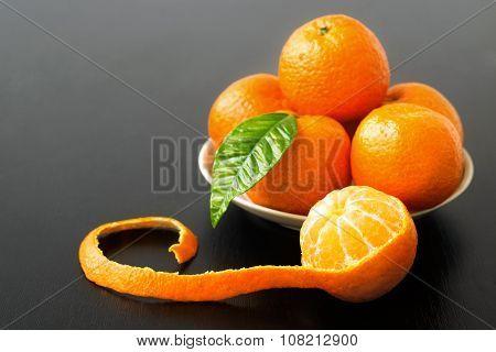 sweet sour peeled tangerine orange and leaf on plate