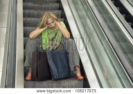 Portrait of a beautiful elegant young blonde woman in the mall escalator with bags.