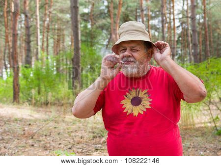 Senior man tasting new home-grown tobacco with cigarette rolled by himself