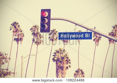 Vintage retro toned Hollywood boulevard sign and traffic lights with palm trees in the background Los Angeles USA. poster