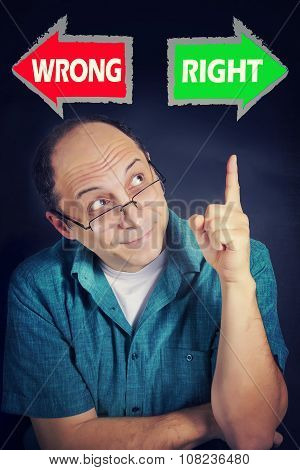Portrait ofAdult man thinking what to choose between RIGHT and WRONG. Grunge background. Pointing on RIGHT poster