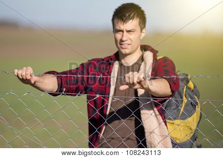 Man Holding Barbed Wire Fence