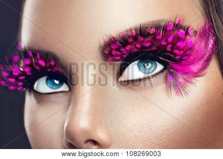 Creative Holiday Makeup. False long purple eyelashes closeup. Beauty model woman face make-up with fantasy bright eyelash