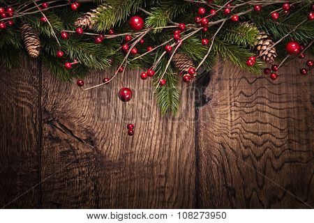 Christmas background with fir branches and berries on wood background
