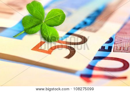 Clover leaf and euros, close-up