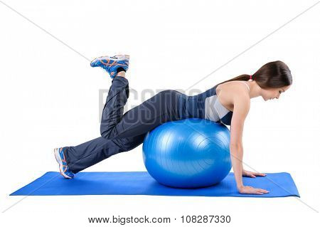 Young woman shows starting position of Fitness Stability Ball Glute Kickback Workout, isolated on white