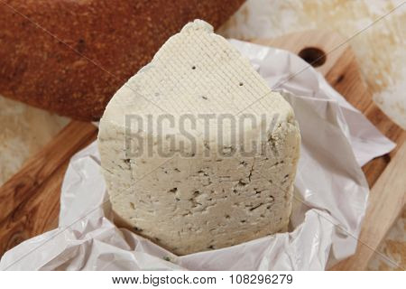 aged italian deli fresh blue stilton cheese and rye ciabatta served on wooden cutting plate on used baking paper as background