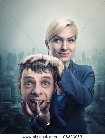 Happy businesswoman with man's head in her hand