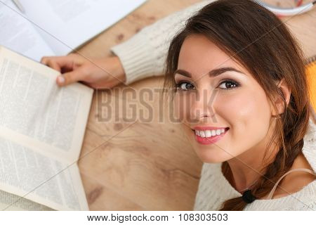 Beautiful Smiling Woman Portrait Lying On Floor Reading Book