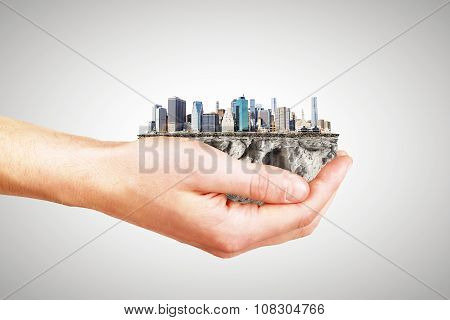 Whole World In One Hand Concept With Man Hand And Part Of Megapolis City District