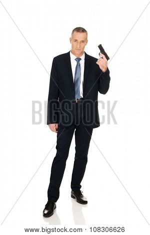 Mature serious mafia agent with handgun. poster