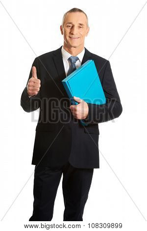 Mature businessman with ok sign holding a binder. poster