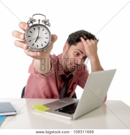 Depressed Businessman Holding Alarm Clock Sitting At Office Desk Working With Computer Laptop In Dea